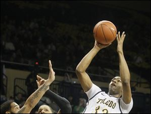 University of Toledo's Curtis Dennis (33) makes a shot after ducking past Cleveland State's Jeremy Montgomery and Aaron Pogue.