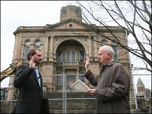 Aaron Montz, 26, left, takes the oath of office from Brent Howard, Tiffin law director, in front of the chain-link fence that surrounds the Seneca County Courthouse. Mr. Montz said Friday he hoped for an order to save the building.