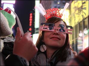 Wearing 2012 glasses and a Happy New Year headpiece, Bernadette Brandl smiles as she takes part in the New Year's Eve festivities in New York's Times Square Saturday. Brandl, who is originally from Austria, is currently living in Minnesota.