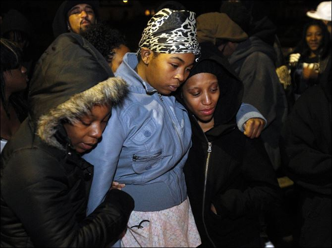 Cousin Antoinette Tilman, left, sister Shavone Belcher, and girlfriend Mariah Livingston hug near a memorial on the corner of Tecumseh and Hoag in honor of Deadrick Rocker, the city's 38th homicide victim.