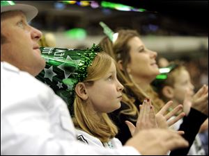 Dallas Stars fans, from left, Chad Hill, Lainie, 8, Casi and Jayce, 5, cheer in the third period while wearing New Year's Eve hats during an NHL hockey game against the Boston Bruins.