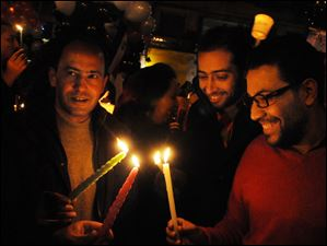 Egyptians light candles during New Year's eve in Tahrir Square, Cairo, Egypt.
