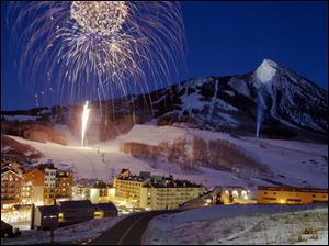 Crested Butte Mountain lit up with new year's eve fireworks as a spotlight shows off the mountain peak in the night sky on Saturday.