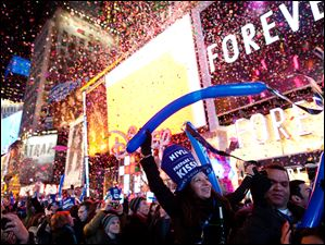 Revelers cheer at midnight in Times Square on New Years Eve in New York as confetti rains down upon them.
