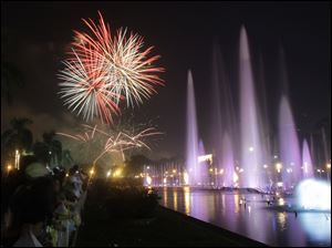 Filipinos watch a fireworks and water fountain display as they welcome the New Year at Manila's Rizal Park, Philippines.