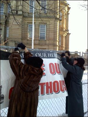 Lenora Livingstone, left, of Tiffin, and Brenda Stultz, of Adams Twp. attach a sign to the fencing around the Seneca County courthouse.