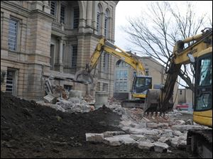 Heavy machinery is used as crews demolish the large staircase leading to the west side of the Seneca County Courthouse.