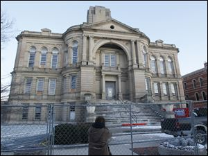 Suzanne Smith, of Tiffin, takes photographs of the county courthouse on the morning of its scheduled demolition.