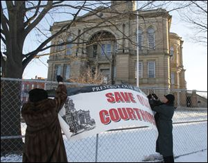 Lenora Livingston of Tiffin, left, and Brenda Stultz of northeastern Seneca County's Adams Township fasten a banner in front of the 1884 Beaux Arts-style  courthouse.