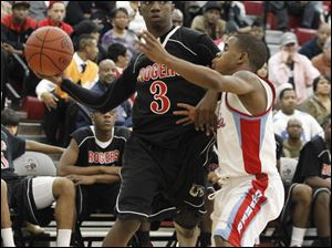 Rogers' Tony Kynard passes the ball while Bowsher's Kharri Dailey defends.