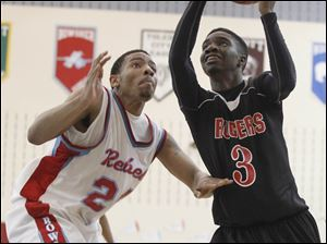 Rogers' Tony Kynard takes the ball to the hoop past the defense of  Bowsher's Mookie Mustafaa.