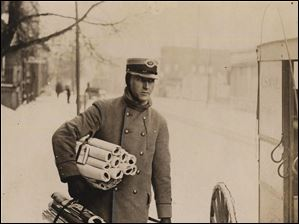 RFD carrier Charles L. Hicks tucks bundles of Toledo mail under his arm in this undated photo.