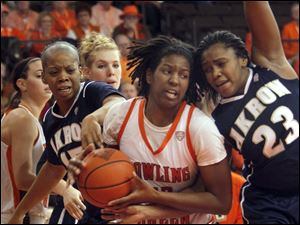BGSU's Alexis Rogers grabs one of her five offensive rebounds of the game, as she is sandwiched by Akron's Ti'eshia Stubbs (15) and  Jasmine Mushington (23).