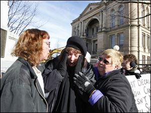 Brenda Stultz, center, is consoled by Lin Talbot-Koehl, left, and Marietta Estep, after she became distraught during the demolition.