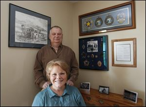 A collection of Alaska State Trooper memorabilia provides a backdrop for Tim Hunyor, and his wife, Sandy Gable Hunyor, in their Portage home. Mr. Hunyor retired after nearly 30 years service.