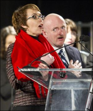 "U.S Rep. Gabrielle Giffords recites the ""Pledge of Allegiance"" alongside her husband Mark Kelly, right, at the start of a vigil at the University of Arizona in Tucson, Ariz., on Sunday, Jan. 8, 2012. The day marks the one year anniversary of the shootings at the Safeway in Tucson."