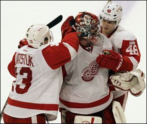 Detroit Red Wings goalie Ty Conklin (29) celebrates with Pavel Datsyuk (13) and Cory Emmerton (48) after they defeated the Chicago Blackhawks 3-2 in an NHL hockey game in Chicago, Sunday.