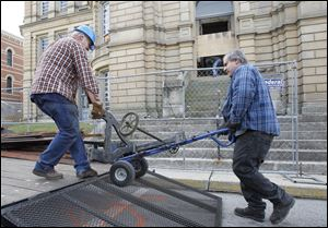 David Kreais, owner of Antiques Warehouse, left, and his brother Ken Kreais, load the mechanism Seneca County Courthouse clock onto a trailer. The pair were salvaging items from the courthouse before demolition.