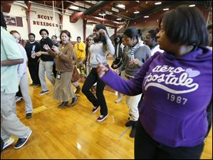 Scott High School special education teacher Andreanai Allen (long skirt), teaches the new 'Bulldog Hustle' dance to seniors in the gym following the tour.