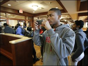 Senior Daqueze Stephens, 17, photographs the school's media center during a tour of the renovated building. Flat screen TVs adorn many of the hallways and common rooms' walls. The TVs will be used, among other things, for morning announcements.