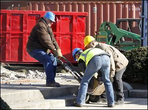 Workers remove the one of the cornerstones.