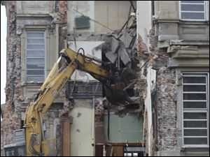 A backhoe tears into the wall of the courthouse.