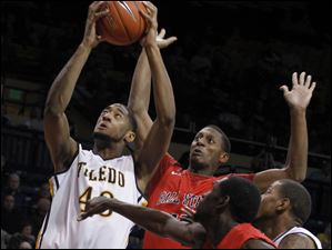 UT's Matt Smith grabs a rebound with Ball State's Jarrod Jones defending during game at UT's Savage Arena in Toledo, Ohio.