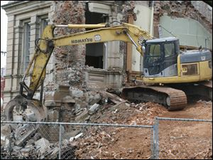 An excavator picks up the cornerstone, containing a time capsule.