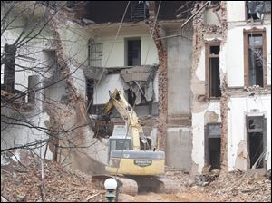 An excavator tears at the walls of the courthouse.
