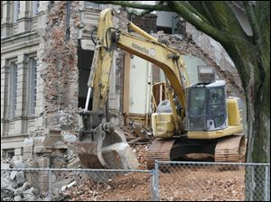 An excavator carries  the cornerstone.