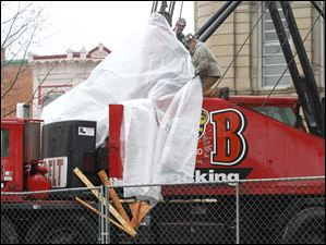 Workers from B&B Wrecking drape their broken crane with plastic, so they can be protected from the elements while making repairs.