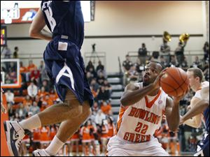 BGSU guard Dee Brown (22) looks for an opening against Akron forward Nikola Cvetinovic (13).