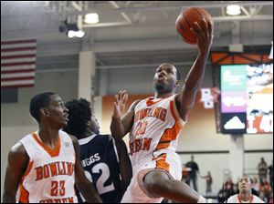 BGSU guard Dee Brown (22) goes to the net against Akron forward Quincy Diggs (22) as Falcons forward Craig Sealey (23) looks on.