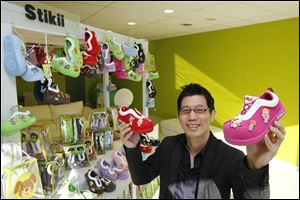 Stikii Shoes owner Joe Chew shows off his product, a line of shoes that children can decorate with color patches and emblems. Mr. Chew also owns Computer Discount, a chain of home computer stores.