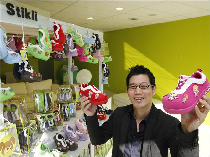 new business looks to find its footing  Stikii Shoes owner Joe Chew shows off his product, a line of shoes that children can decorate with color patches and emblems. Mr. Chew also owns Computer Discount, a chain of home computer stores.
