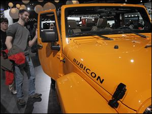 Auburn Hills, Mich. resident Jeff Rice checks out a Jeep Rubicon during the North American International Auto Show in Detroit, Mich.