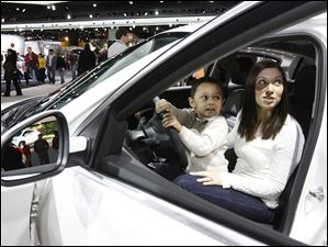 Gabriel McCarter, 3, with his mom, Katherine McCarter, of Monroe, Mich., looks at the back seat of a Buick 2012 Regal GS during the North American International Auto Show in Detroit, Mich.