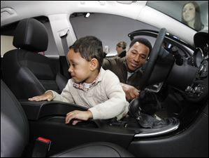 Gabriel McCarter, 3, with his dad, John McCarter, of Monroe, Mich. looks at the back seat of a Buick 2012 Regal GS during the North American International Auto Show in Detroit, Mich.