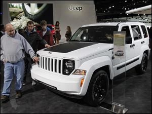 Howell, Mich. residents Pat Dowd, from left, and his sons Colin and Nolan, feel the hood of a Jeep Liberty during the North American International Auto Show in Detroit, Mich.