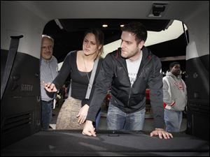 Toledo residents Stephanie Schilling and her fiance, Aaron Knight, right, explore the back of a 2012 Acadia Denali a during the North American International Auto Show in Detroit, Mich.