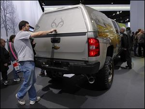 Waterford, Mich. resident Jeff Fendelet opens the back of a Chevy Silverado during the North American International Auto Show in Detroit, Mich.