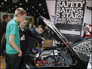 From left: John Nagelkirk, Adam Oakley and Perrysburg, Ohio resident Michael Davisson look at the engine of a Toyota Camry during the North American International Auto Show in Detroit, Mich.