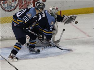Walleye goalie Dustin Carlson makes one of his 25 saves in the game. His teammate is Phil Rauch (20).