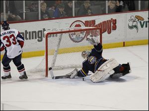 Walleye goalie Dustin Carlson makes a stop of a shot by the Wings' Kory Karlander during the shootout.