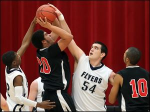 Lake High School's Marcus Pierce blocks a shot by Fostoria's Adonis Cousin (20) Tuesday, at Owens Community College in Perrysburg Township.
