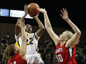 Toledo's Andola Dortch (22) takes a shot at the net between Ball State forward Suzanne Grossnickle (00) and guard Brandy Woody (11).