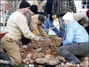 Chris Babione, left, and Kathy Zellner, right, are among the people bundled up against the cold on Wednesday as they dig through a pile of bricks after excavators dumped them over the construction fence.
