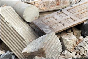 A door, a column, and other pieces of stone lie in a pile inside the fence. People picked through the debris to find bricks and other items outside the fence, including pieces of the black fossilized marble once on the upper floors.