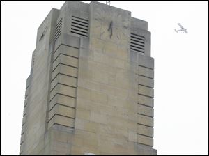 A plane flies near the clock tower.