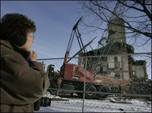 Seneca County resident Suzanne Smith watches the demolition.